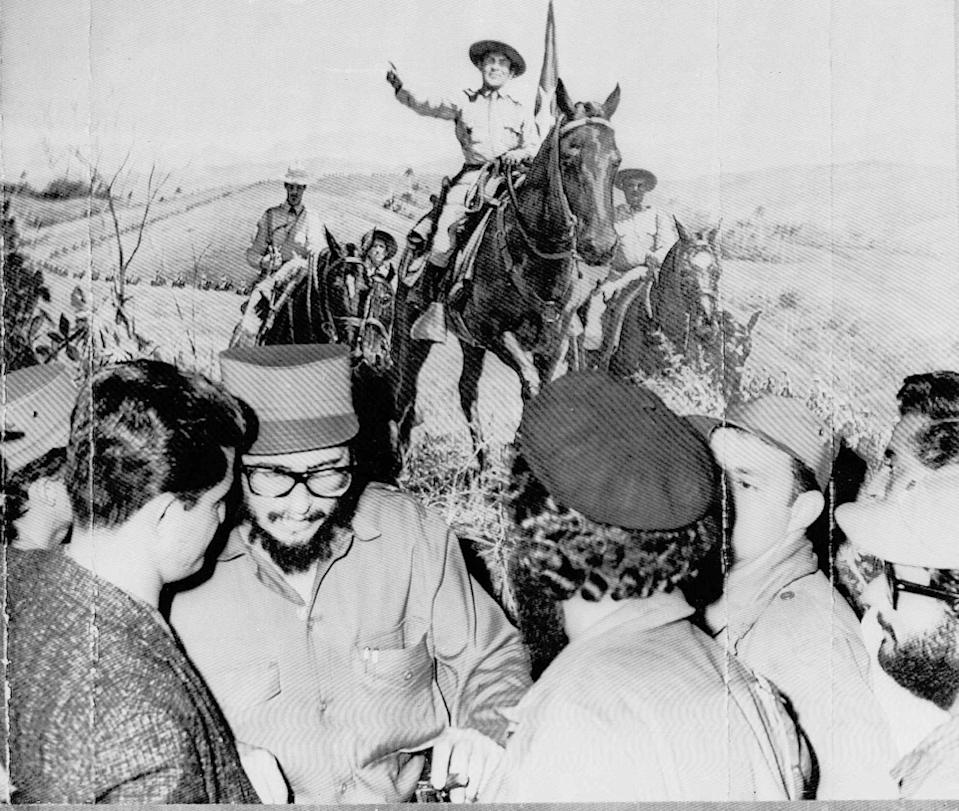 <p>Fidel Castro is shown in 1959 with a group of his soldiers in front of a mural showing ex-dictator Fulgencio Batista as an army Colonel leading troops through mountains of eastern Cuba. Castro viewed the mural at Batista's farm 15 miles southwest of Havana. (AP Photo) </p>