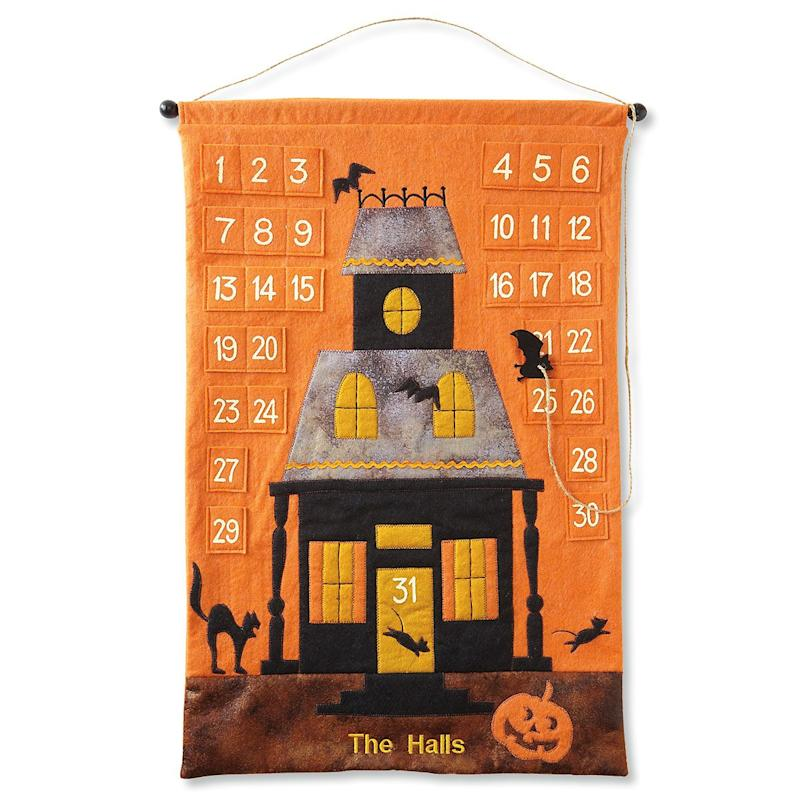 Orange felt wall hanging with 31 pockets and a haunted house design