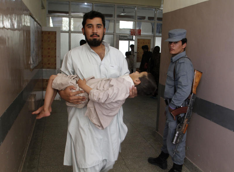 An Afghan doctor carries a boy for treatment at a hospital after a suicide bomb explosion in Kandahar province, southwest of Kabul, Afghanistan, Saturday, Aug. 31, 2013. A suicide bomber detonated his explosives near a police checkpoint and a bank in southern Afghanistan on Saturday, killing several people, officials said. Most of the victims were civilians. Along with the badly damaged branch building of the New Kabul Bank, several small shops and vehicles were damaged. (AP Photo/Allauddin Khan)