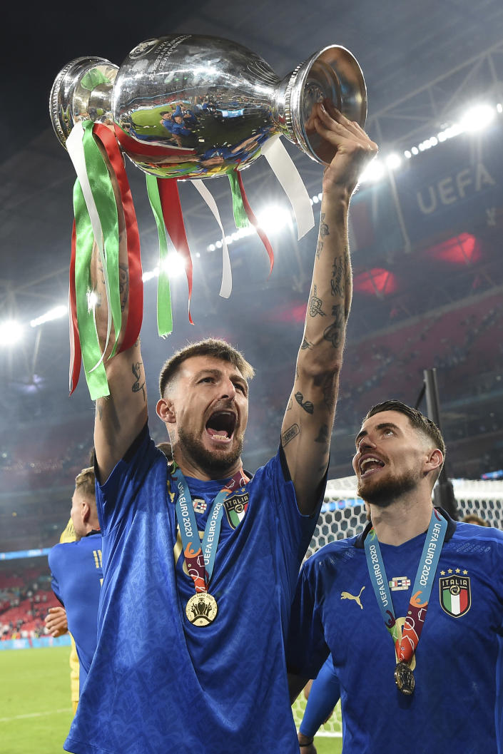 Italy's Francesco Acerbi holds up the trophy after the final of the Euro 2020 soccer final match between England and Italy at Wembley stadium in London, Sunday, July 11, 2021. (Andy Rain/Pool Photo via AP)