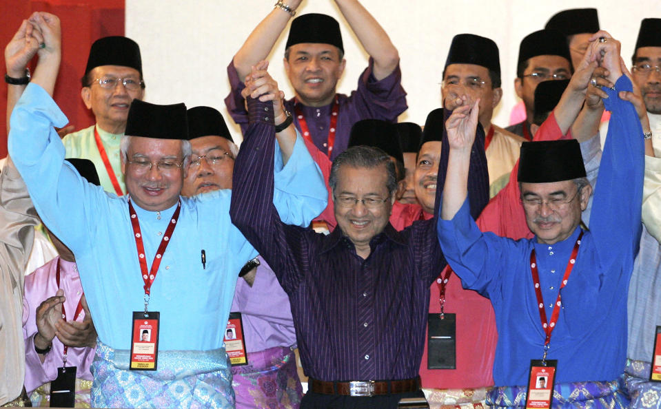 Then Malaysia's former Prime Minister Mahathir Mohamad, center, raises hands with then Prime Minister Abdullah Ahmad Badawi, right, and then Deputy Prime Minister Najib Razak at the United Malays National Organization (UMNO) general assembly in Kuala Lumpur, Malaysia, on March 28, 2009. Former Prime Minister Najib was found guilty Tuesday, July 28, 2020 in his first corruption trial linked to one of the world's biggest financial scandals - the billion-dollar looting of the 1MDB state investment fund. (AP Photo/Lai Seng Sin)
