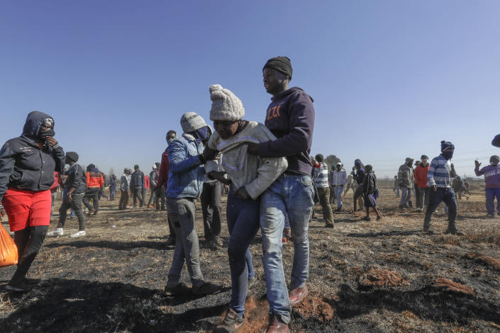 Residents help a family member of a 14-year-old boy who was shot during protests in Vosloorus, east of Johannesburg, South Africa, Wednesday July 14, 2021. South Africa's rioting continued Wednesday as police and the military struggle to quell the violence in Gauteng and KwaZulu-Natal provinces. The violence started in various parts of KwaZulu-Natal last week when Zuma began serving a 15-month sentence for contempt of court. (AP Photo/Themba Hadebe)