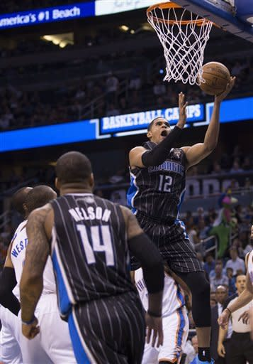 Orlando Magic's Tobias Harris (12) lays up the ball for two points against the Oklahoma City Thunder defense during the first half of an NBA basketball game on Friday, March 22, 2013, in Orlando, Fla. (AP Photo/Willie J. Allen Jr.)