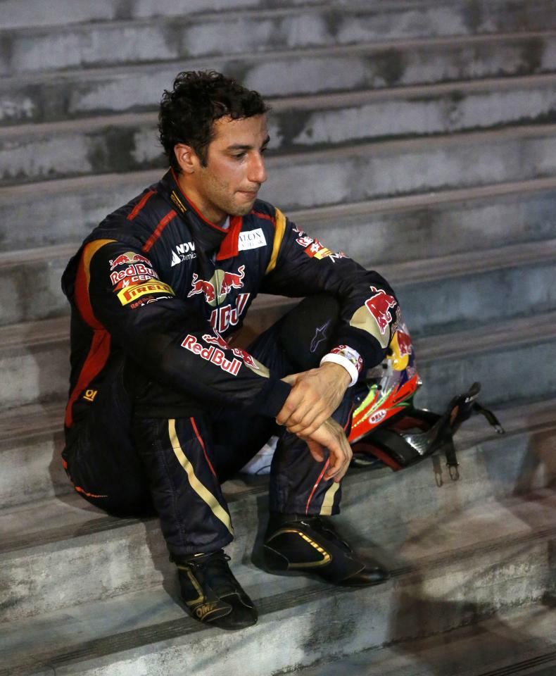 Toro Rosso Formula One driver Daniel Ricciardo of Australia sits down on steps after crashing during the Singapore F1 Grand Prix at the Marina Bay street circuit in Singapore September 22, 2013. REUTERS/Natashia Lee (SINGAPORE - Tags: SPORT MOTORSPORT F1)
