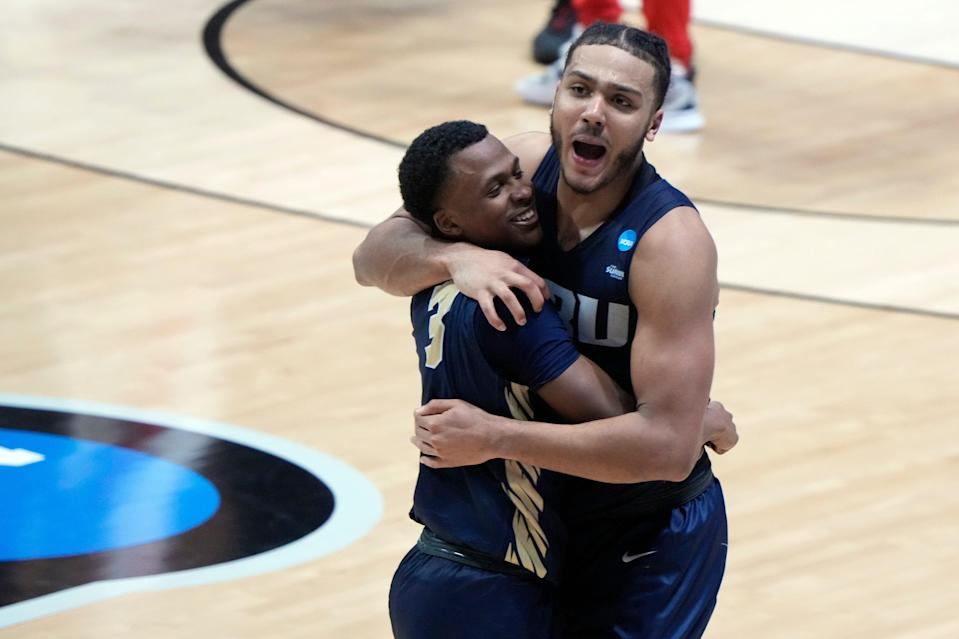 Oral Roberts guard Max Abmas (3) and forward Kevin Obanor (0) celebrate after the Golden Eagles' overtime victory over Ohio State in the first round.