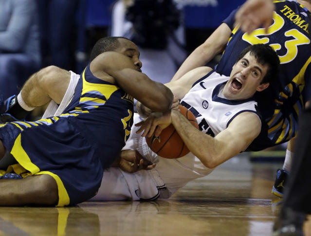 Butler guard Alex Barlow, right, and Marquette guard Derrick Wilson fight for a loose ball in the first half of an NCAA college basketball game in Indianapolis, Saturday, Jan. 18, 2014. (AP Photo/Michael Conroy)