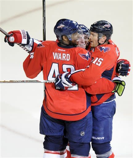 Washington Capitals center Keith Aucoin, center, celebrates his goal with teammates Joel Ward (42) and Jeff Halpern (15) during the first period of an NHL hockey game against the Tampa Bay Lightning, Thursday, March 8, 2012, in Washington. (AP Photo/Nick Wass)