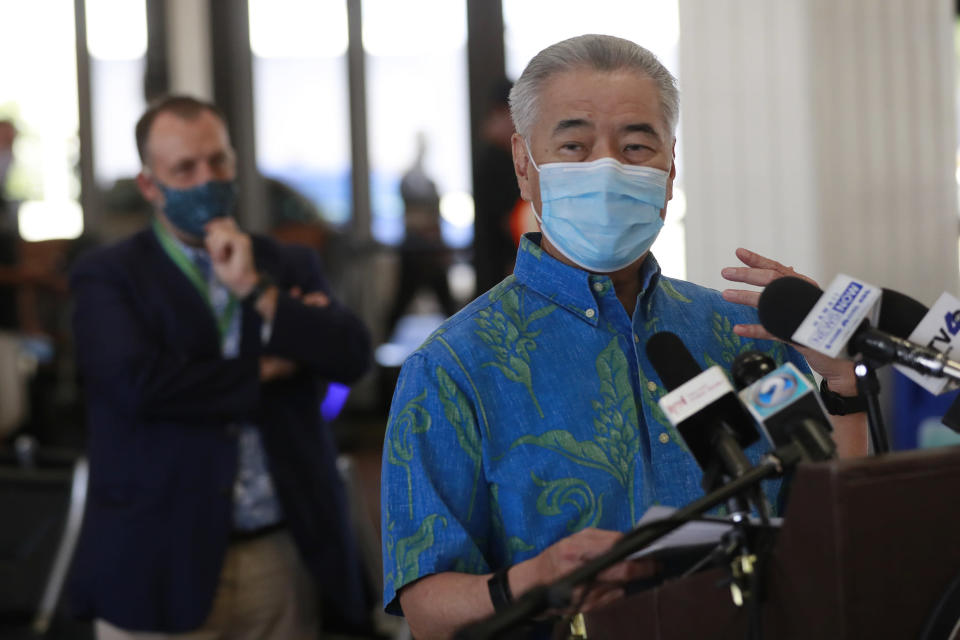 With Hawaii Lt. Gov. Josh Green, left background, looking on, Hawaii Gov. David Ige speaks at a news conference at the Daniel K. Inouye International Airport, Thursday, Oct. 15, 2020, in Honolulu. A new pre-travel testing program that will allow visitors who test negative for COVID-19 to come to Hawaii and avoid two weeks of mandatory quarantine went into effect Thursday. (AP Photo/Marco Garcia)