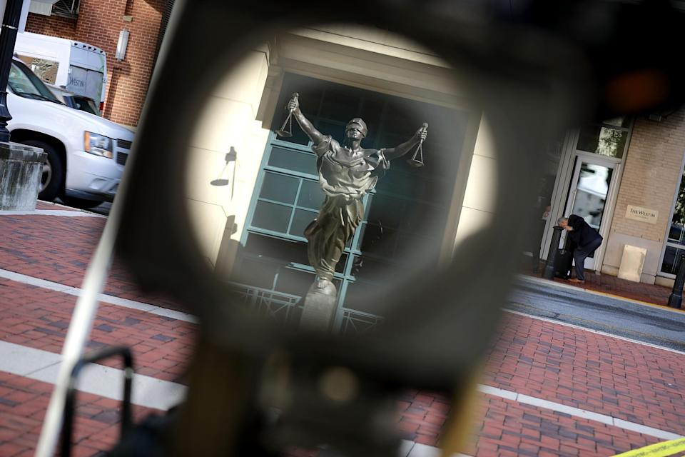 <p>The statue of Justice outside the Albert V. Bryan U.S. Courthouse is reflected in a television news camera lens on the second day of former Trump campaign chairman Paul Manafort's trial August 1, 2018 in Alexandria, Va. (Photo: Chip Somodevilla/Getty Images) </p>