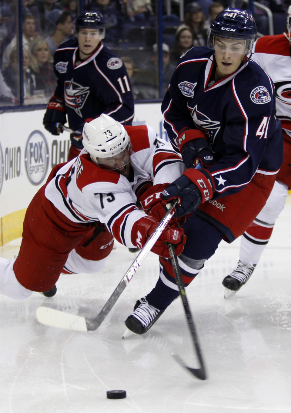Carolina Hurricanes' Brett Bellemore, left, and Columbus Blue Jackets' Alexander Wennberg, of Sweden, reach for the puck during the second period of an NHL hockey game in Columbus, Ohio, Tuesday, Nov. 4, 2014. (AP Photo/Paul Vernon)