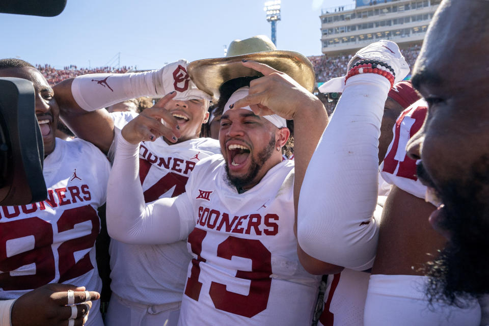 Oklahoma quarterback Caleb Williams (13) puts on the Golden Hat after coming off the bench to lead Oklahoma to a 54-48 win over Texas in an NCAA college football game at the Cotton Bowl, Saturday, Oct. 9, 2021, in Dallas. (AP Photo/Jeffrey McWhorter)