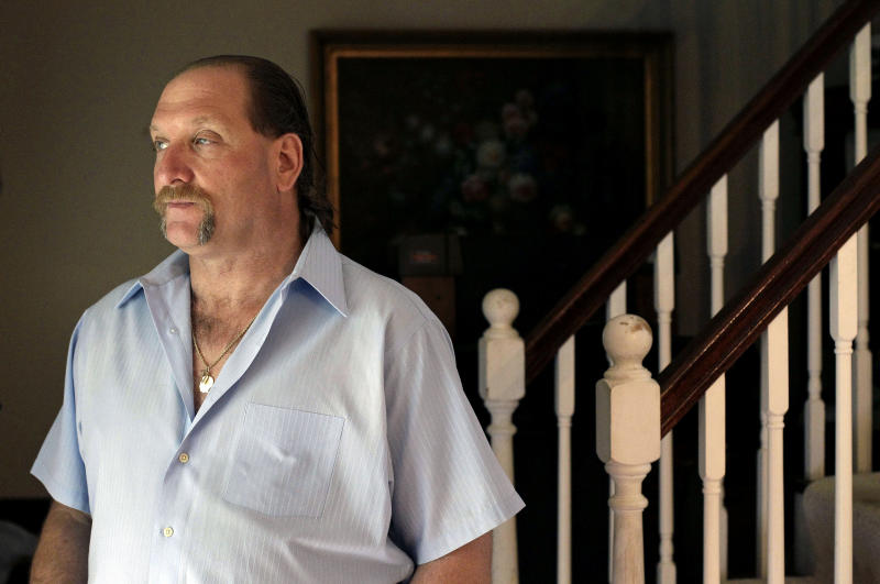 """In this May 3, 2012 photo, breast cancer survivor Robert Kaitz stands in his living room in Severna Park, Md. Kaitz thought a small growth under his left nipple was just a harmless cyst. By the time he had it checked out in 2006, almost two years later, the lump had started to hurt. The diagnosis was a shock. """"I had no idea in the world that men could even get breast cancer,"""" Kaitz said. Now Kaitz does frequent self-exams and has mammograms every year. The American Cancer Society estimates 1 in 1,000 men will get breast cancer, versus 1 in 8 women. (AP Photo/Patrick Semansky)"""