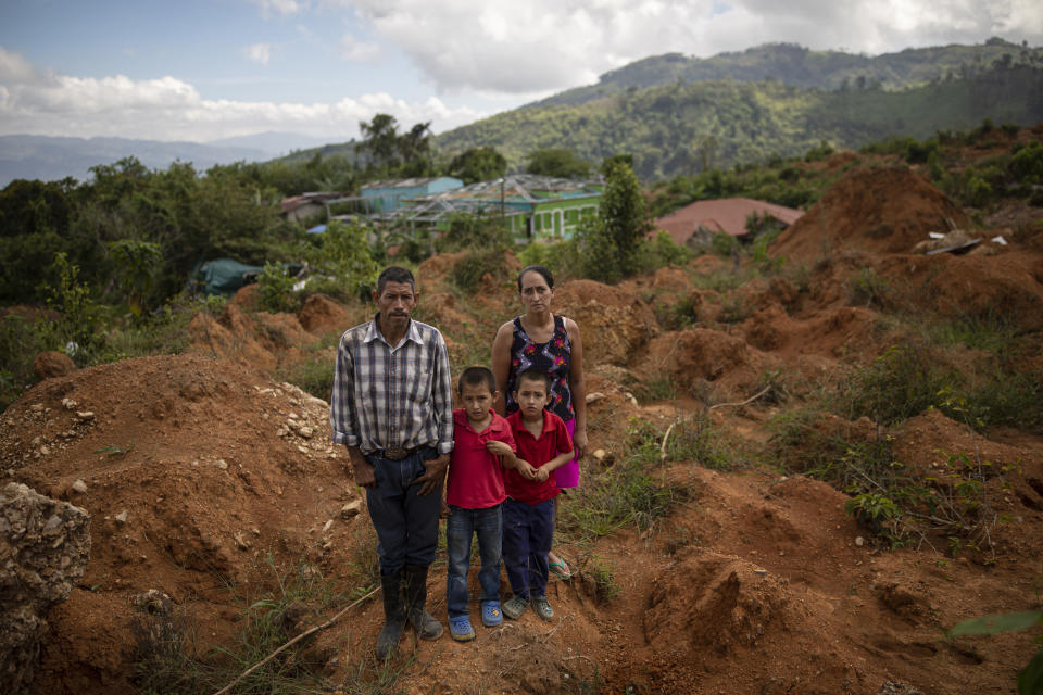 Eleuterio Esquivel, 51, left, poses with his wife, Elsa Mejia, 40, and their twins, Ibis Esquivel, left, and Noel Esquivel, 7, at the site of their home destroyed by a landslide triggered by hurricanes Eta and Iota in the village of La Reina, Honduras, Wednesday, June 23, 2021. Home to about 1,000 people, the town in western Honduras was hit by two powerful hurricanes within three weeks, natural disasters made far worse by local deforestation and climate change. La Reina was buried by a landslide. (AP Photo/Rodrigo Abd)