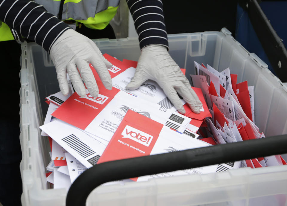 In this March 10, 2020, file photo wearing gloves, a King County Election worker collect ballots from a drop box in the Washington State primary in Seattle. Washington is a vote by mail state.  (AP Photo/John Froschauer, File)