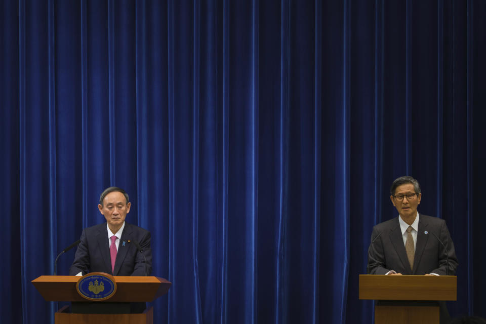 FILE - In this Dec. 25, 2020, file photo, Japan's Prime Minister Yoshihide Suga, left, and government taskforce chief Shigeru Omi attend a press conference on the COVID-19 situation in Japan at the prime minister's office in Tokyo. Prime Minister Suga came to office on a surge of popularity, pledging to combat the coronavirus and fix the languishing economy. Now his support ratings have plunged amid flaring virus outbreaks and scandals within the ruling party, even as the economy appears to be recovering. (Nicolas Datiche/Pool Photo via AP, File)
