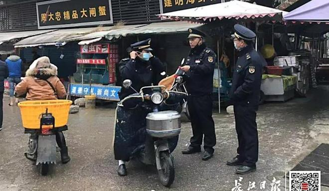 Law enforcement officers stand guard outside the market in Wuhan. Photo: Yangtze Daily
