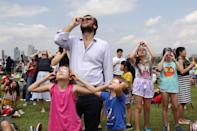 """A man and his daughters watching the annular solar eclipse from the Marina Barrage on 26 December. Read our story: <a href=""""https://bit.ly/2SybMEO"""" rel=""""nofollow noopener"""" target=""""_blank"""" data-ylk=""""slk:https://bit.ly/2SybMEO"""" class=""""link rapid-noclick-resp"""">https://bit.ly/2SybMEO</a> (PHOTO: Dhany Osman / Yahoo News Singapore)"""