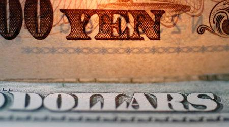 "FILE PHOTO - The word ""Yen"" is pictured on a Japanese banknote on top of a U.S. dollar bill at Interbank Inc. Money exchange in Tokyo, Japan in this September 9, 2010 picture illustration.  REUTERS/Yuriko Nakao/File Photo"