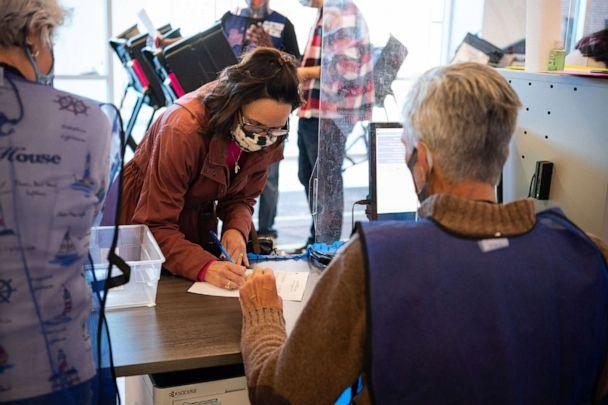 PHOTO: Election official Scott Hagara checks in a voter at the board of elections headquarters during early voting on Oct.16, 2020 in Painesville, Ohio. (Dustin Franz/AFP via Getty Images, FILE)