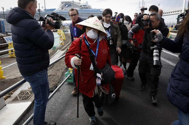 A passenger is surrounded by the media after she disembarked from the quarantined Diamond Princess cruise ship on Wednesday: AP