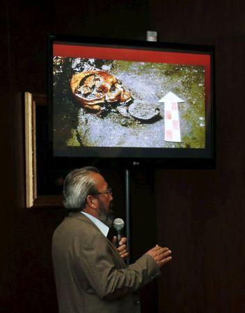 Raul Barrera, an archaeologist from the National Institute of Anthropology and History (INAH), speaks to the media as a picture of a skull that was discovered at the ruins of the Templo Mayor Aztec complex is seen above him, during a news conference at the Anthropology Museum in Mexico City August 20, 2015. REUTERS/Henry Romero