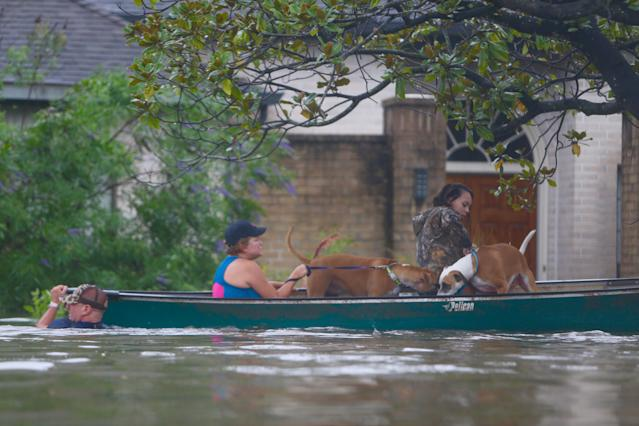 <p>A family evacuates their Meyerland home in Houston, Aug. 27, 2017. Rescuers answered hundreds of calls for help Sunday as floodwaters from the remnants of Hurricane Harvey rose high enough to begin filling second-story homes, and authorities urged stranded families to seek refuge on their rooftops. (Photo: Mark Mulligan/Houston Chronicle via AP) </p>