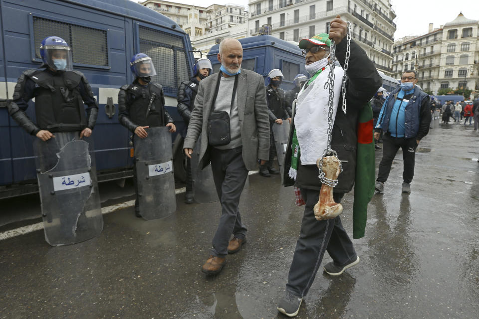 "A man holds a bone while shouting ""That's what's left for those who vote for the President"" as Algerians demonstrate in Algiers to mark the second anniversary of the Hirak movement, Monday Feb. 22, 2021. February 22 marks the second anniversary of Hirak, the popular movement that led to the fall of Algerian President Abdelaziz Bouteflika. (AP Photo/Anis Belghoul)"