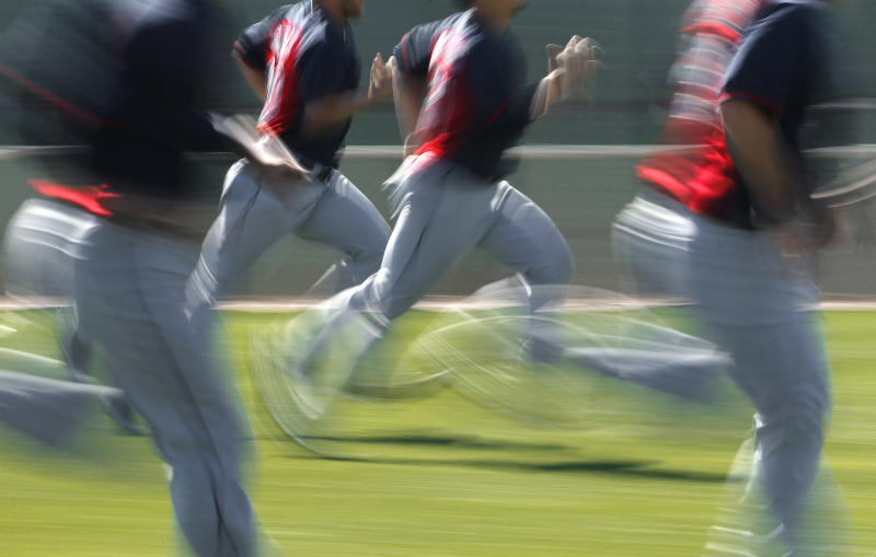 In this image taken with a slow shutter speed, Cleveland Indians players run during spring training baseball practice in Goodyear, Ariz., Thursday, Feb. 13, 2014. (AP Photo/Paul Sancya)