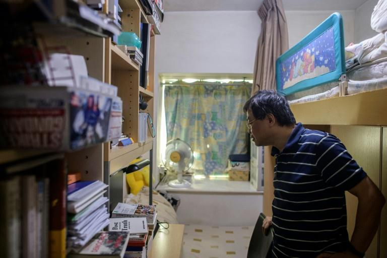 Roger Wong, looking at shelves in Joshua's room, says he was open-minded about his son's studies and always knew he was politically minded