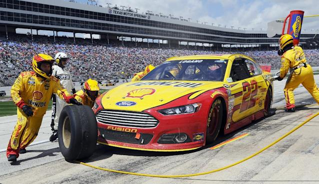 Joey Logano (22) gets fuel and tires during a pit stop during the NASCAR Sprint Cup series auto race at Texas Motor Speedway, Monday, April 7, 2014, in Fort Worth, Texas. (AP Photo/Ralph Lauer)