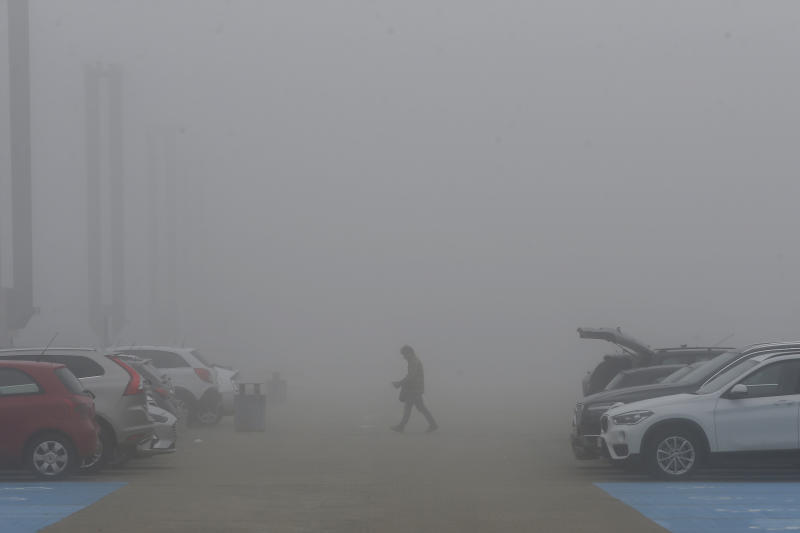 A man crosses the car park in thick fog outside the COP25 summit in Madrid, Spain, Tuesday, Dec. 10, 2019. The 2-week global U.N. sponsored climate change conference is taking place in Madrid. (AP Photo/Paul White)