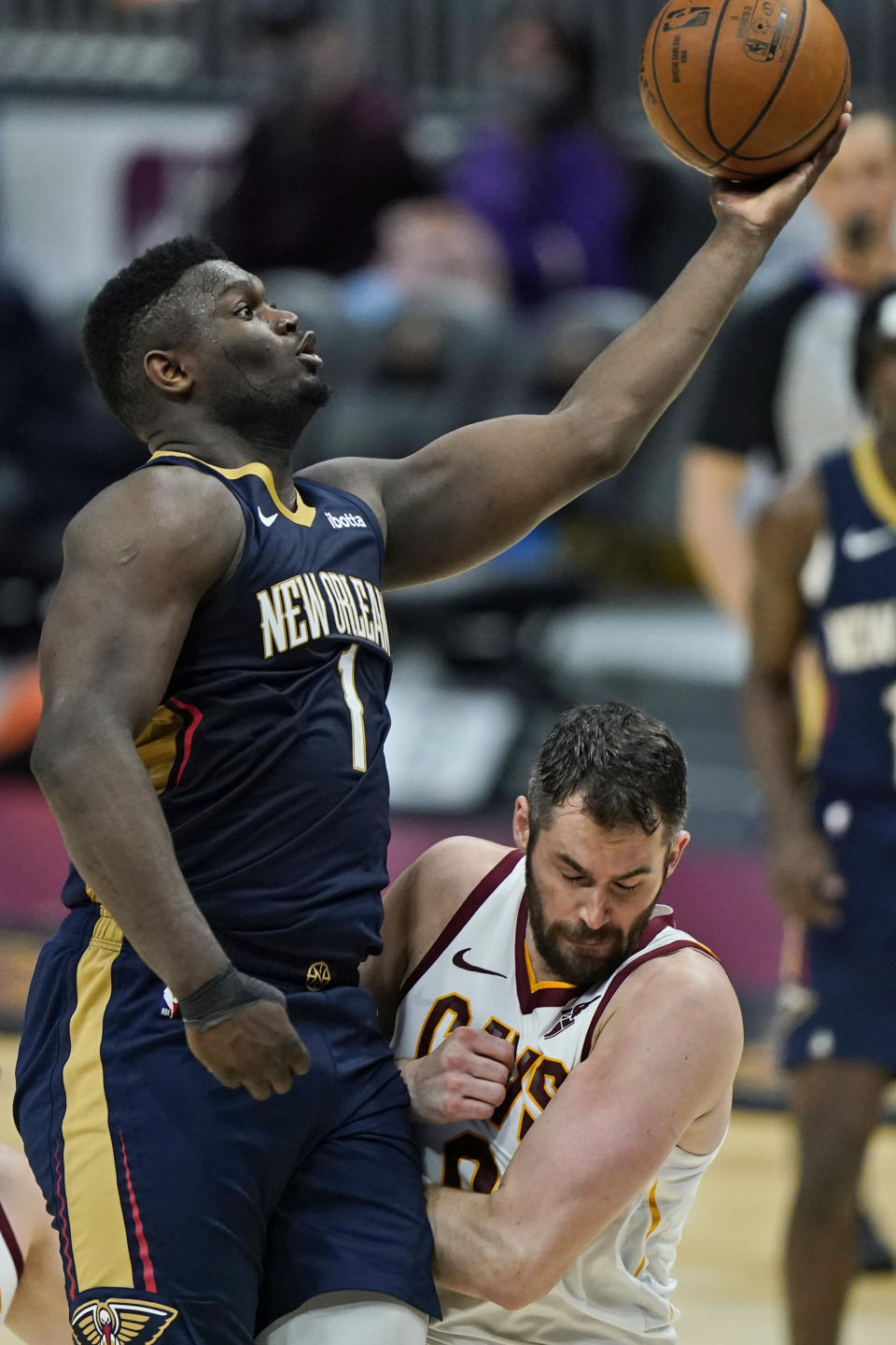 New Orleans Pelicans' Zion Williamson, left, drives to the basket against Cleveland Cavaliers' Kevin Love in the second half of an NBA basketball game, Sunday, April 11, 2021, in Cleveland. (AP Photo/Tony Dejak)
