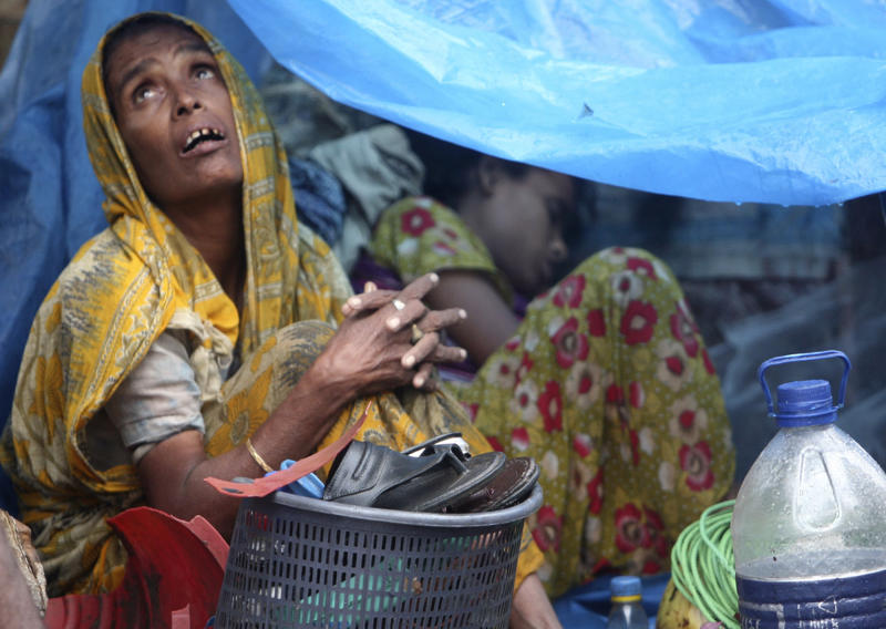 FILE - In this July, 28, 2009 file photo, a Bangladeshi woman looks skyward from inside her temporary home, a tent set up on the roadside, in Dhaka, Bangladesh as heavy monsoon rains have battered Bangladesh's capital, flooding streets and homes, stranding thousands and forcing businesses and schools to close. Experts say Asia and the South Pacific, home to 4.3 billion people or 60 percent of all humankind, faces rising risks from climate change that threaten food security, public health and social order, in a report given Monday, March 31, 2014 by a United Nations scientific panel meant to guide policymakers and form the foundation for a new climate treaty due next year. (AP Photo/Pavel Rahman, File)