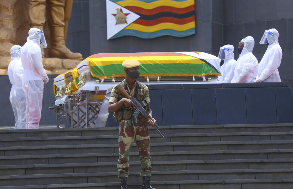 Pallbearers stand next to the coffins of three top government officials prior to their burial, at the National Heroes Acre in Harare, Wednesday, Jan. 27, 2021. Zimbabwe on Wednesday buried three top officials who succumbed to COVID-19, in a single ceremony at a shrine reserved almost exclusively for the ruling elite as a virulent second wave of the coronavirus takes a devastating toll on the country. (AP Photo/Tsvangirayi Mukwazhi)