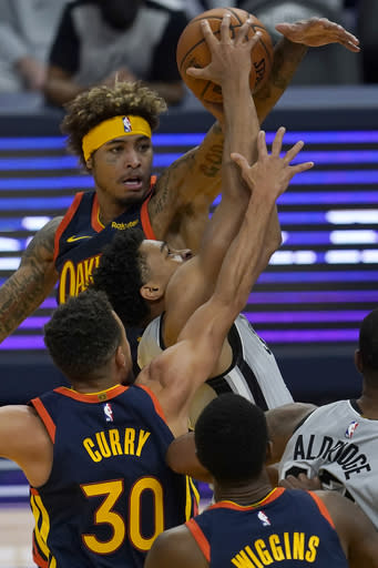 San Antonio Spurs forward Keldon Johnson, middle, shoots between Golden State Warriors guard Stephen Curry (30) and guard Kelly Oubre Jr. during the second half of an NBA basketball game in San Francisco, Wednesday, Jan. 20, 2021. (AP Photo/Jeff Chiu)