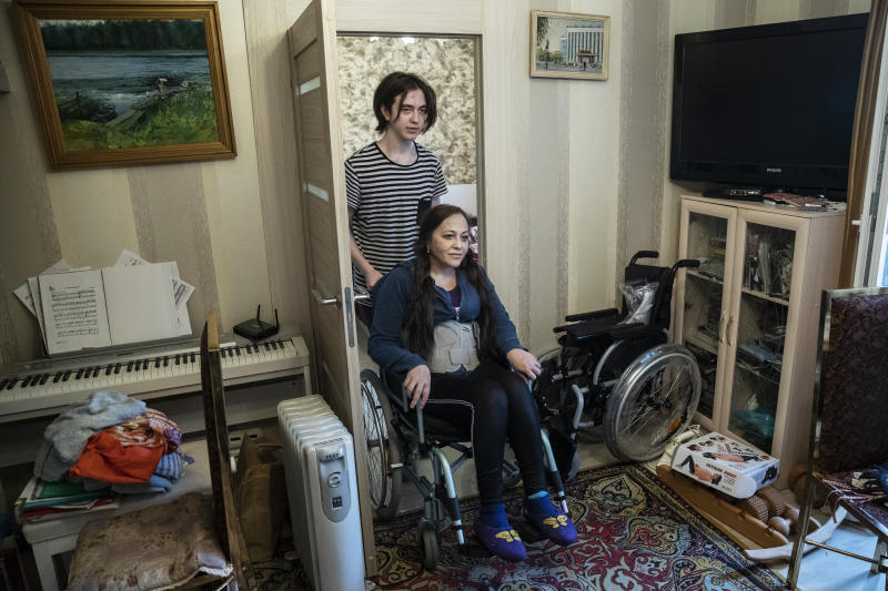 In this May 26, 2020, photo, Irina Karabulatova is pushed in a wheelchair by her son, Mikhail, in their apartment in Moscow, Russia. A smartphone app designed to track Moscow's quarantined coronavirus patients was rolled out by city officials in early April, but complaints about it have mushroomed. Karabulatova, a bed-ridden professor who hasn't left her apartment in a year, was fined for not installing the mandatory app. After her story made national headlines, the fines were canceled and officials apologized. (AP Photo/Pavel Golovkin)