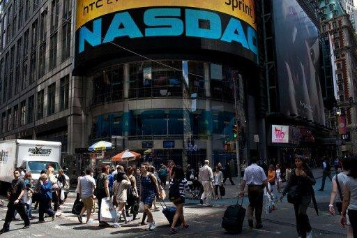 People are seen walking past the Nasdaq exchange in Time Square, New York, in June. Facebook reports its first earnings as a public company on Thursday in an announcement that will be closely watched for signs of whether the social media giant can deliver on its financial promise