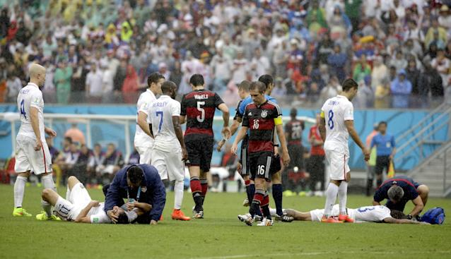 United States' Alejandro Bedoya, left, and United States' Jermaine Jones lie on the pitch after colliding during the group G World Cup soccer match between the USA and Germany at the Arena Pernambuco in Recife, Brazil, Thursday, June 26, 2014. (AP Photo/Ricardo Mazalan)