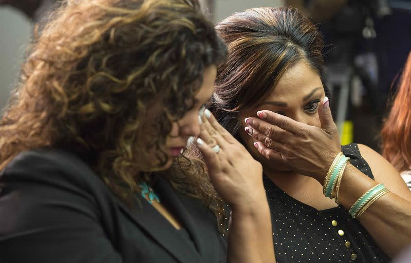 Family members of GM crash victims wipe their eyes as Kenneth Feinberg, a victims compensation lawyer hired by GM, speaks in Washington