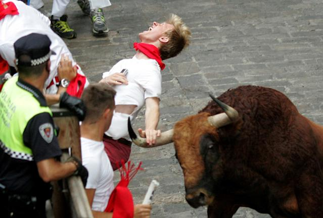 """A runner is gored by an """"El Pilar"""" fighting bull during the running of the bulls at the San Fermin festival, in Pamplona, Spain, Friday, July 12, 2013. An American and two Spaniards were gored Friday during a danger-filled sixth bull run of Spain's San Fermin festival, with one loose bull causing panic in the packed streets of Pamplona city. (AP Photo/ Olivia Aguirre)"""