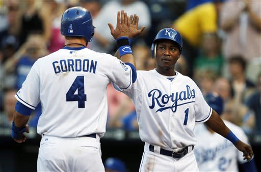 Kansas City Royals' Alex Gordon (4) is congratulated by Jarrod Dyson (1) after both were driven home on a double by Billy Butler during the first inning of a baseball game against the New York Yankees in Kansas City, Mo., Saturday, May 5, 2012. (AP Photo/Orlin Wagner)