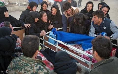 Devastated families gather around one of the victims in Sarpol-e Zahab county in Kermanshah - Credit: Reuters