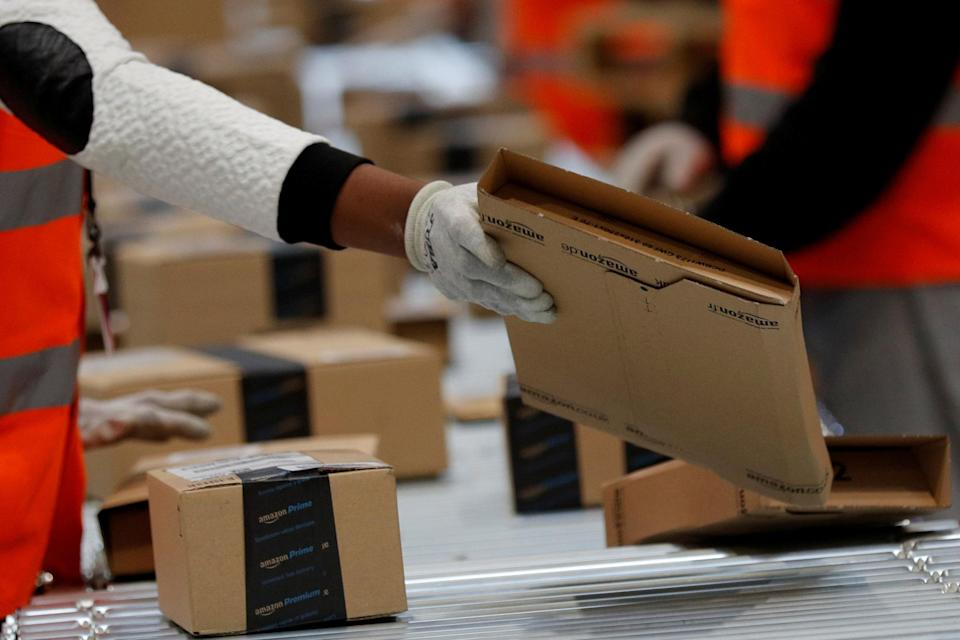 Employees sort packages at the Amazon distribution center warehouse in Saran, near Orleans, France. REUTERS/Philippe Wojazer