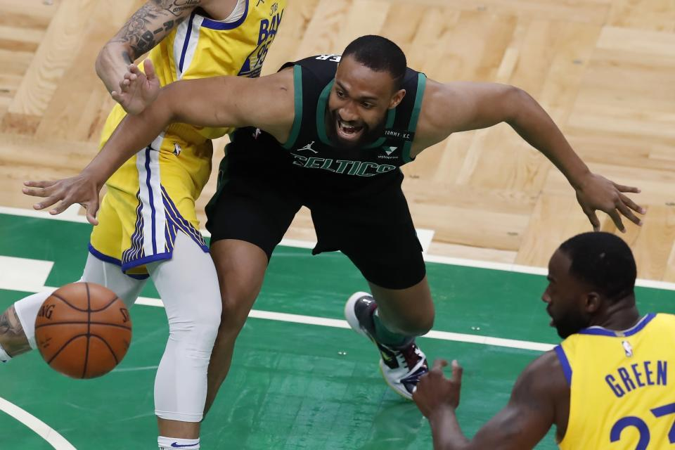 Boston Celtics'Jabari Parker, center, and Golden State Warriors' Draymond Green (23) scramble for the ball during the first half of an NBA basketball game, Saturday, April 17, 2021, in Boston. (AP Photo/Michael Dwyer)