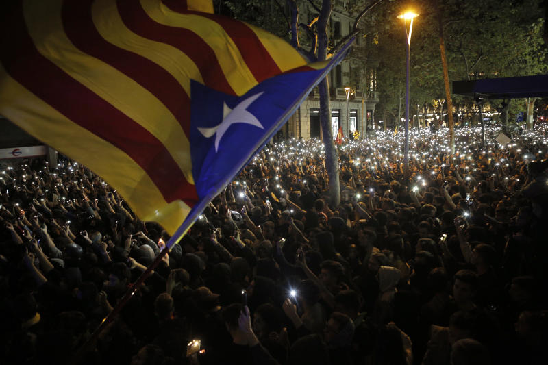 A pro-independence Estelada flag is waved above demonstrators holding up their cellphones during a protest in Barcelona, Spain, Tuesday, Oct. 15, 2019. (Photo: Joan Mateu/AP)
