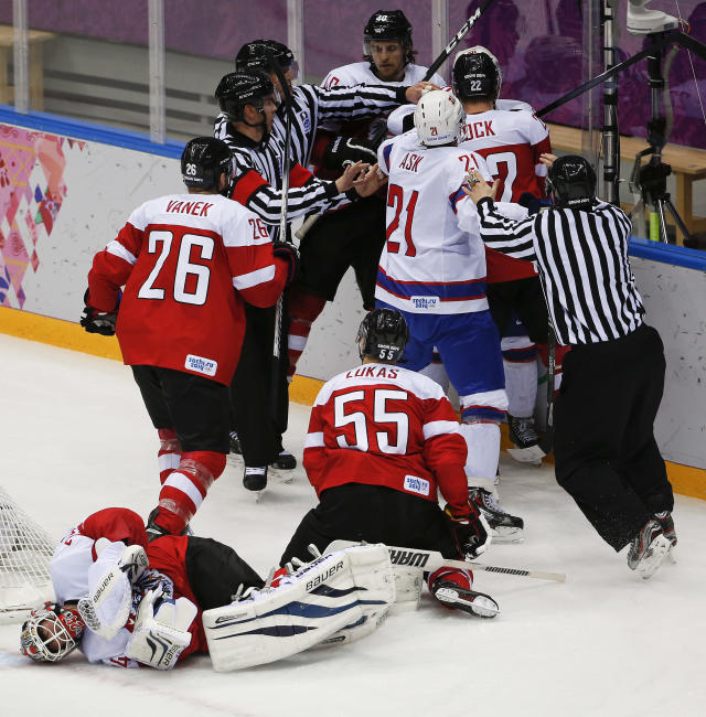 Officials move in to break up a scuffle after a collision by a player from Norway with Austria goaltender Mathias Lange period of a men's ice hockey game at the 2014 Winter Olympics, Sunday, Feb. 16, 2014, in Sochi, Russia. (AP Photo/Julio Cortez)