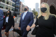 John Wilson, center, holds his wife's hand, right, as he leaves the John Joseph Moakley Federal Courthouse after the first day of his trial in the college admissions scandal, Monday, Sept.13, 2021, in Boston. (AP Photo/Stew Milne)