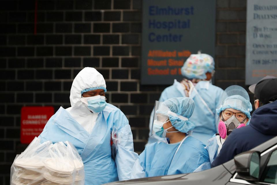 Healthcare workers wearing personal protection equipment (PPE) take a food delivery outside Elmhurst Hospital Center ,as the spread of the coronavirus disease (COVID-19) continues, in the Queens borough of New York City, U.S., April 24, 2020. REUTERS/Lucas Jackson