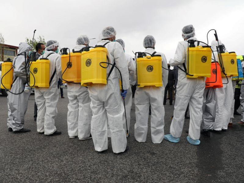 Volunteers prepare to spray disinfectant along a street to prevent the spread of the coronavirus disease (COVID-19) in Kabul