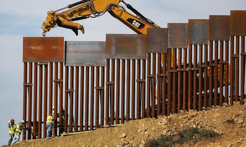 A construction crew installs new sections of the US-Mexico border barrier on 11 January.